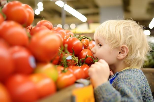 Chłopiec w supermarkecie wybiera świeżych organicznie pomidory