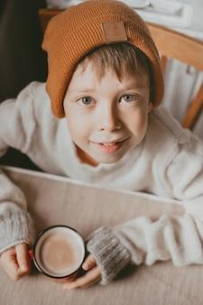Chłopiec w swetrze i brązowym kapeluszu pije kakao z czerwonego kubka. przytulne zdjęcie z kubkiem w dłoni. chłopiec z dużymi oczami wygląda z dołu, widok z góry