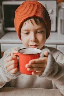 Chłopiec w swetrze i brązowym kapeluszu pije kakao z czerwonego kubka. przytulne zdjęcie z kubkiem w dłoni.