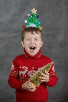 Chłopiec w świątecznym swetrze i obręczy choinki z małą choinką.