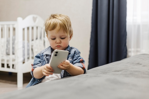 Chłopiec w sypialni przy użyciu telefonu komórkowego