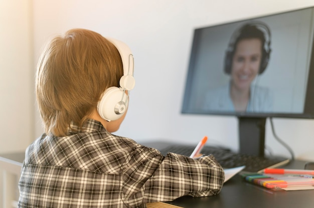 Chłopiec w szkole bierze udział w kursach online i nosi słuchawki