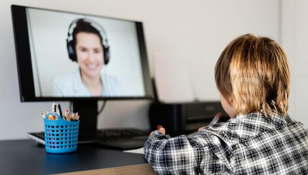 Chłopiec w szkole bierze udział w kursach online