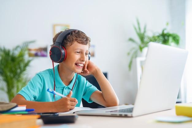 Chłopiec w szkole na wideokonferencji z nauczycielem na laptopie