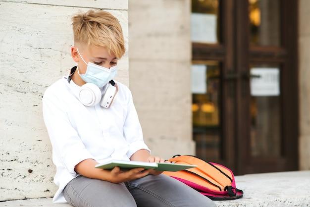 Chłopiec w szkole noszący maskę na twarz do ochrony przed koronawirusem. powrót do koncepcji szkoły. edukacja w czasie pandemii. zmęczony chłopiec w masce ochronnej po lekcjach. koronawirus i życie szkolne.