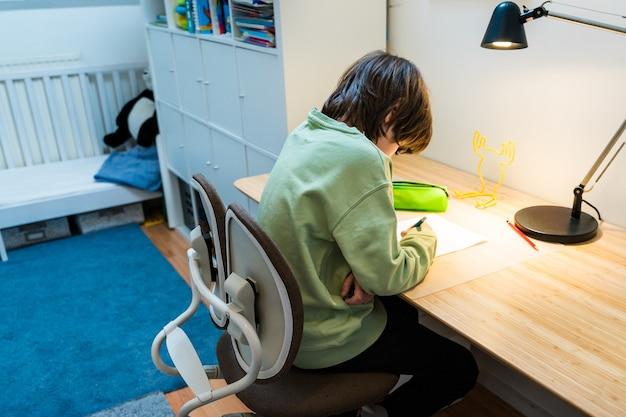 Chłopiec w szkole odrabia lekcje, siedząc na krześle ortopedycznym przy stole w domu. skoncentrowane ćwiczenia pisania dla dzieci. koncepcja homeschooliong.