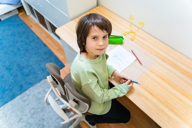 Chłopiec w szkole odrabia lekcje, siedząc na krześle ortopedycznym przy stole w domu. skoncentrowane dziecko pisze ćwiczenia z przyjemnością. koncepcja homeschooliong.