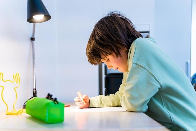 Chłopiec w szkole odrabia lekcje, siedząc przy stole w domu. skoncentrowane ćwiczenia pisania dla dzieci. koncepcja homeschooliong.
