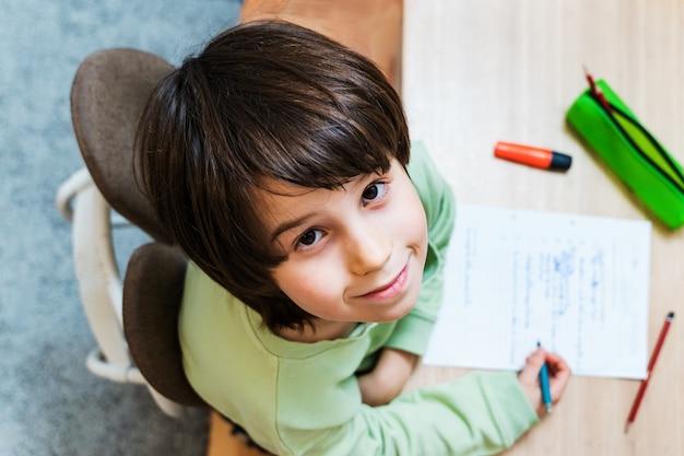 Chłopiec w szkole odrabia lekcje, siedząc przy stole w domu. skoncentrowane ćwiczenia pisania dla dzieci z przyjemnością. koncepcja homeschooliong.