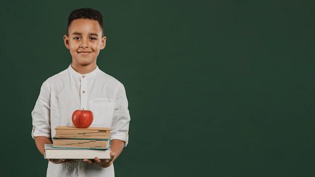 Chłopiec w szkole trzyma książki i jabłko