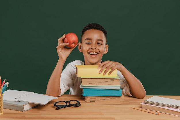Chłopiec w szkole trzyma pyszne jabłko