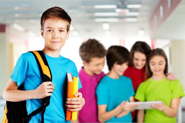 Chłopiec w szkole z książkami i plecakiem