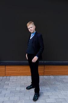 Chłopiec w szkolnym mundurku na czarnej ścianie, z powrotem do szkoły