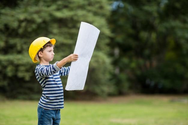 Chłopiec w twardy kapelusz czyta plan