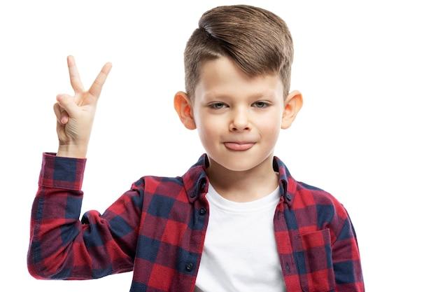 Chłopiec w wieku 7 lat pokazuje ręką znak zwycięstwa. zbliżenie. na białym tle na białej ścianie.