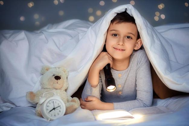 Chłopiec w wieku 8-9 lat czyta wieczorem w ciemności pod kocem z latarką książkę