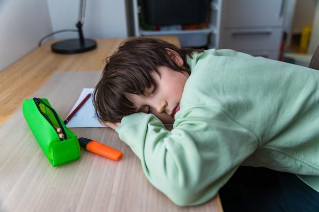 Chłopiec w wieku dziesięciu lat odrabia lekcje, siedząc przy stole w domu. zmęczone dziecko śpi podczas ćwiczeń szkolnych twarzą na biurku.