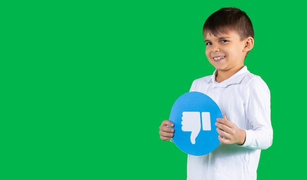 Chłopiec w wieku przedszkolnym z szyderczą twarzą trzymającą znak niechęci