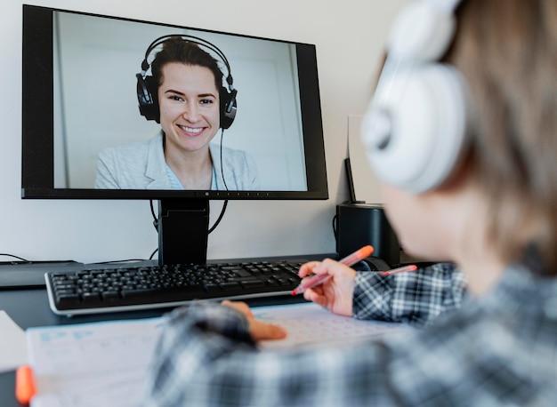 Chłopiec w wieku szkolnym bierze udział w kursach online z nauczycielem