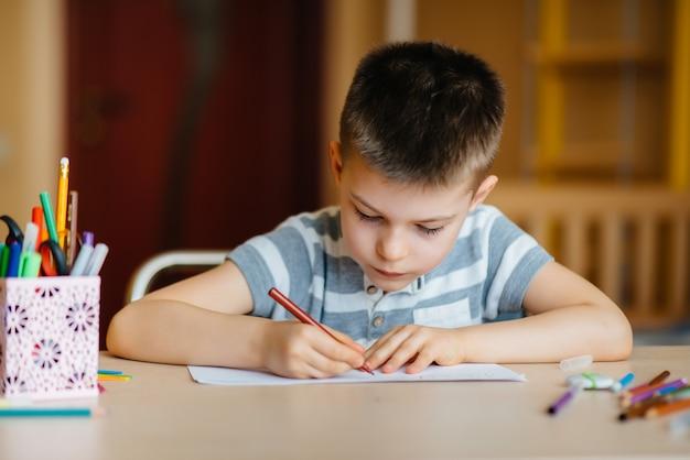 Chłopiec w wieku szkolnym odrabia lekcje w domu. szkolenie w szkole.