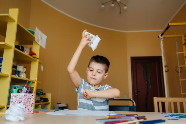 Chłopiec w wieku szkolnym odrabia lekcje w domu. trening w szkole.