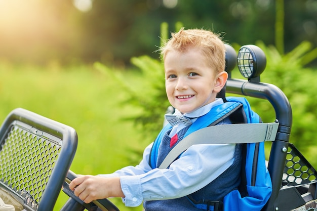 Chłopiec w wieku szkolnym prowadzący samochód dla dzieci z plecakiem