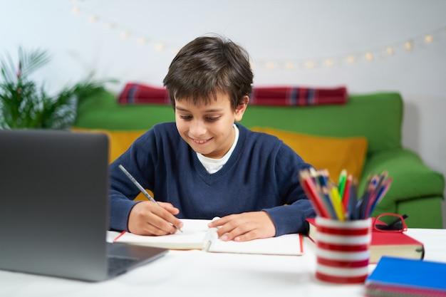 Chłopiec w wieku szkolnym prowadzący zajęcia online, siedząc w domu w kwarantannie, używając laptopa i robiąc notatki