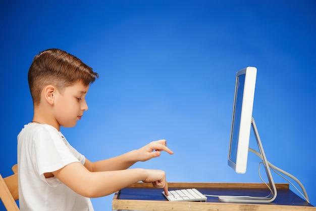Chłopiec w wieku szkolnym siedzi przed monitorem laptopa