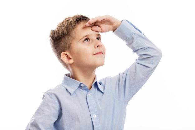 Chłopiec w wieku szkolnym w niebieskiej koszuli patrzy w dal. pojedynczo na białym
