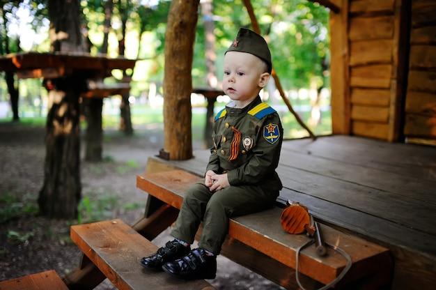 Chłopiec w wojskowym uniformu siedzi na drewnianym domu