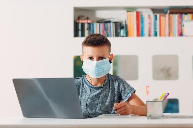 Chłopiec w zestaw słuchawkowy siedzi przy stole z laptopem i maską medyczną i przygotowuje się do szkoły
