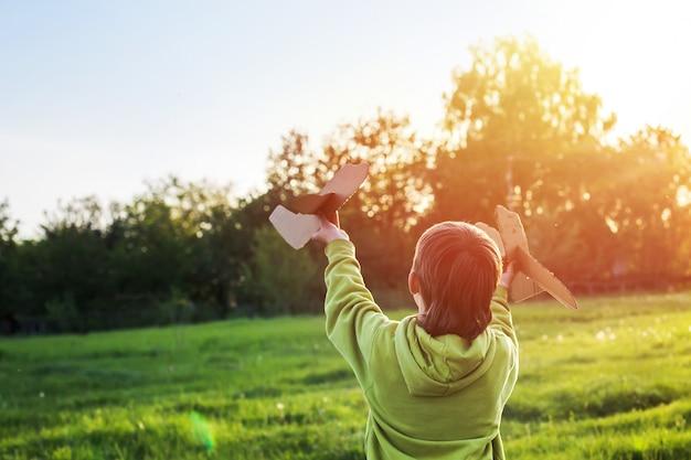 Chłopiec w zielonej kurtce biegnie przez pole o zachodzie słońca