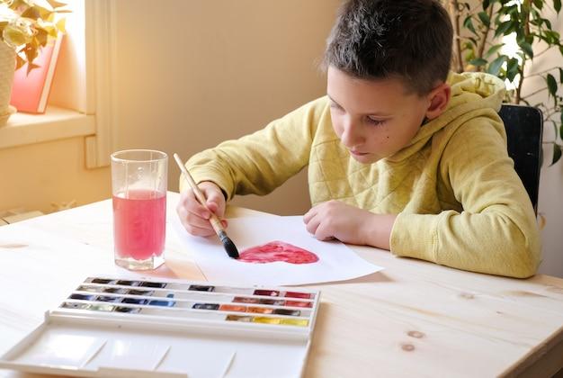 Chłopiec w żółtych ubraniach maluje akwarele serca na walentynki
