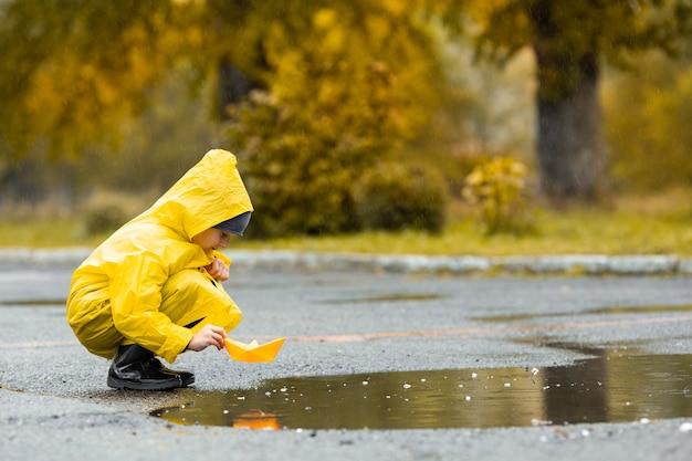 Chłopiec w żółtym nieprzemakalnym płaszczu i czarnych gumowych kaloszach bawi się ręcznie robioną papierową zabawką w kałuży na świeżym powietrzu podczas deszczu jesienią.