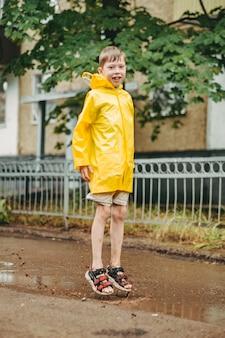 Chłopiec w żółtym płaszczu przeciwdeszczowym wychodzi na zewnątrz w deszczu. dziecko skacze na przewężeniu. skakać przez błotniste kałuże. szczęśliwe i beztroskie dzieciństwo