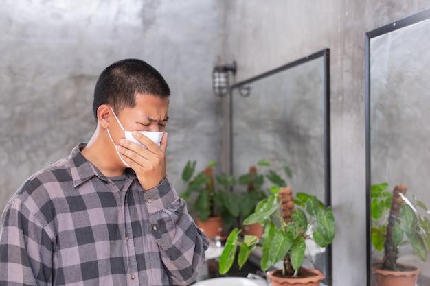 Chłopiec walczy gacenia maskę i zamyka usta ręką dla ochrony wirusa na toalecie. - pojęcie maskowa kampania.