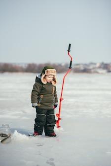 Chłopiec wędkowanie na zimę. ładny chłopak łapie ryby w jeziorze zimą. zimowy. na wolnym powietrzu