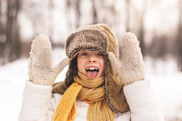 Chłopiec wije się i pokazuje język. portret zimą w przyrodzie