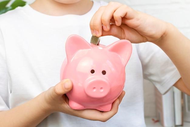 Chłopiec wkłada monety do różowej skarbonki. odpowiedzialność finansowa, akumulacja, planowanie oszczędności.