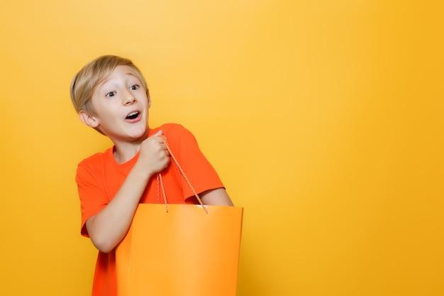 Chłopiec włożył rękę do pomarańczowej papierowej torby i jest szczęśliwy