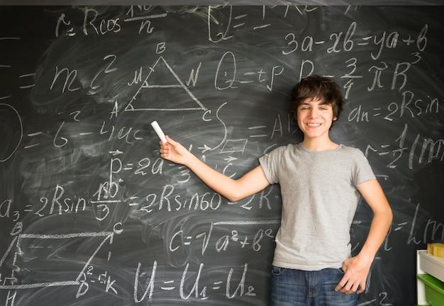 Chłopiec wskazując kredą na pustej czarnej tablicy w tle z formułami matematycznymi w tle