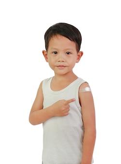 Chłopiec wskazujący z plastrem samoprzylepnym, bawełna ze szczepionych. dziecko z plastrem z zastrzyku
