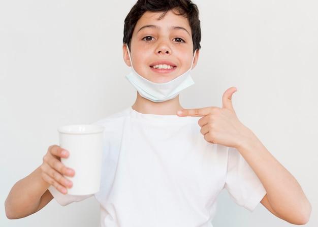 Chłopiec wskazuje przy herbacianą filiżanką