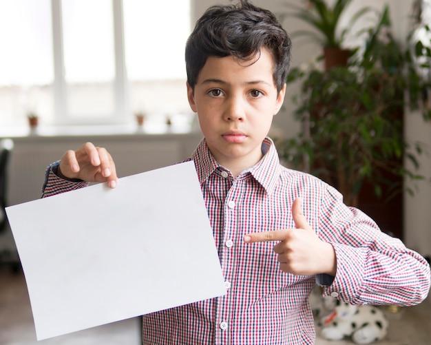 Chłopiec wskazuje przy pustego papieru prześcieradłem