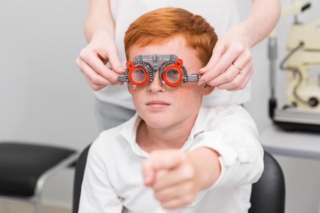 Chłopiec wskazuje w kierunku kamery, podczas gdy kobieta okulista bada jego oczy