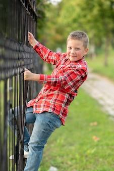 Chłopiec wspiął się na kute ogrodzenie. w dowolnym celu.
