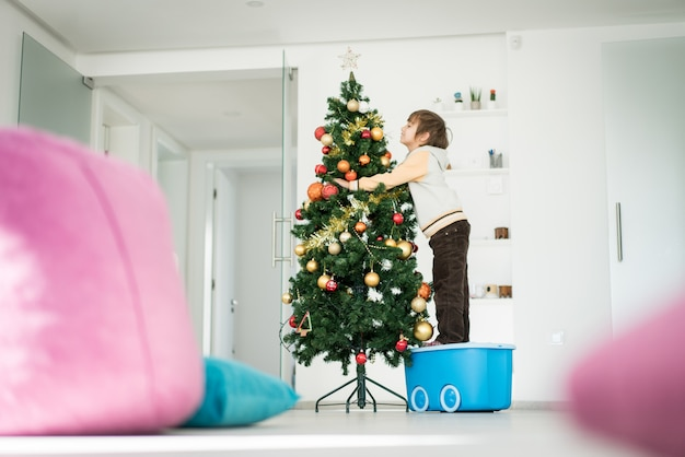 Chłopiec wspina się na zabawkarskim pudełku dekorować choinki