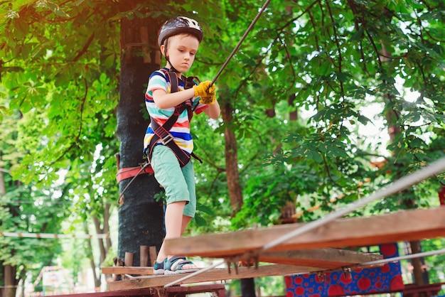 Chłopiec wspina się po parku linowym. mały ładny chłopiec w parku przygód wspinaczki. słoneczny letni dzień. sznurowa konstrukcja placu zabaw. bezpieczna wspinaczka sportowa ekstremalna. dziecko z ubezpieczeniem kasku w parku linowym.