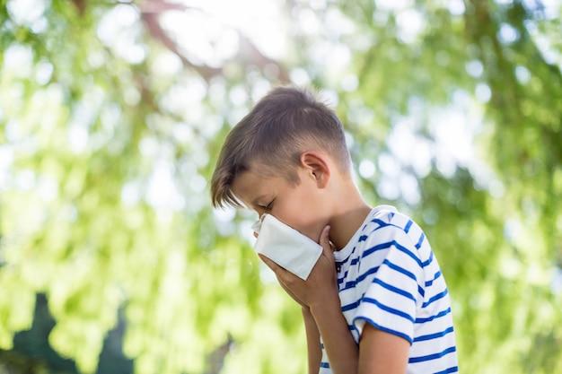 Chłopiec wyciera nos podczas kichania