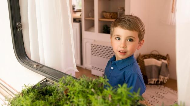 Chłopiec wyglądający przez okno swojej przyczepy kempingowej